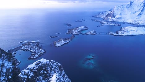 An-Aerial-View-Shows-Snowcovered-Mountains-And-Bridges-On-The-Lofoten-Islands-Norway