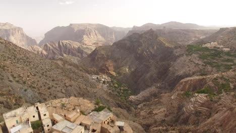 Una-Vista-Aérea-Muestra-Una-Ciudad-Escondida-En-Una-Región-Montañosa-De-Wadi-Shab-Omán