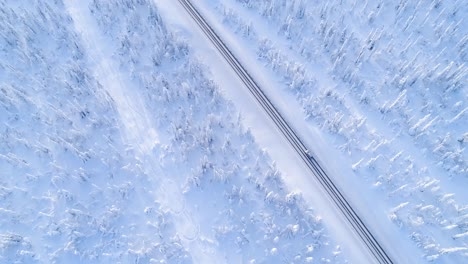 An-Aerial-View-Shows-A-Car-Driving-Down-A-Treelined-Snowcovered-Highway-In-Sweden