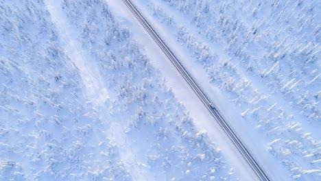 Una-Vista-Aérea-Muestra-Un-Automóvil-Conduciendo-Por-Una-Autopista-Cubierta-De-Nieve-Arbolada-En-Suecia