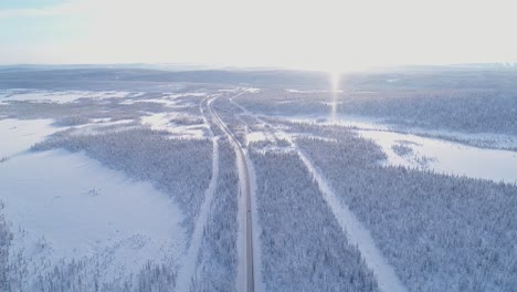 An-Vista-Aérea-View-Shows-A-Car-Driving-Down-A-Treelined-Snowcovered-Highway-In-Sweden-1