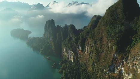 Eine-Luftaufnahme-Zeigt-Grüne-Berge-Und-Hafenunterkünfte-Zwischen-Den-Wolken-Im-Khao-Sok-Nationalpark-In-Surat-Thani-Thailand