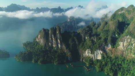 Eine-Luftaufnahme-Zeigt-Grüne-Berge-Und-Hafenunterkünfte-Zwischen-Den-Wolken-Im-Khao-Sok-Nationalpark-In-Surat-Thani-Thailand-2
