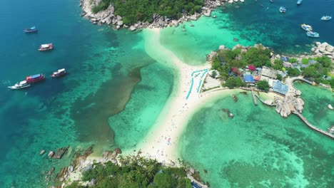 An-Aerial-View-Shows-Boats-Anchored-Near-And-Tourists-Relaxing-On-The-Interconnected-Ko-Tao-Islands-In-Thailand