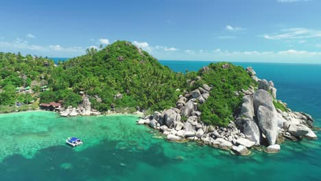 An-Aerial-View-Shows-A-Boat-Anchored-Near-A-Rocky-Harbor-On-Ko-Tao-Thailand