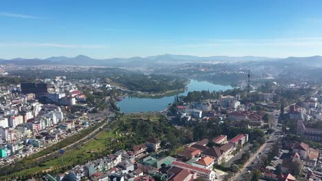 An-Aerial-View-Shows-Buildings-A-Radio-Tower-And-A-Lake-Of-Dalat-Vietnam