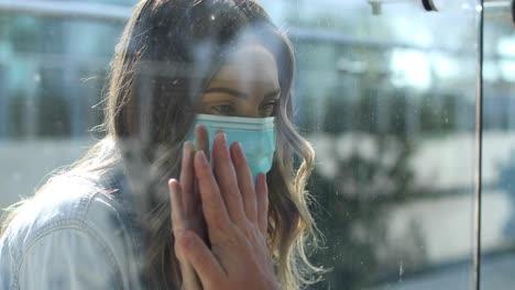 Eine-Gereinigte-Frau-Mit-Maske-Wird-Während-Der-Coronavirus-Pandemie-Durch-Ein-Glasfenster-Von-Einem-Geliebten-Menschen-Getrennt-Oder-Isoliert
