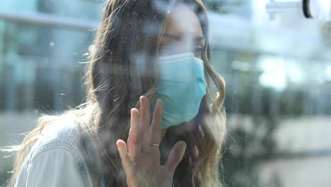 A-cleared-woman-with-mask-is-separated-or-isolated-from-a-loved-one-by-a-glass-window-during-coronavirus-pandemic-1