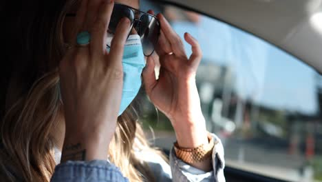 A-woman-puts-on-a-surgical-mask-before-driving-her-car-during-the-Covid19-coronavirus-pandemic-epidemic