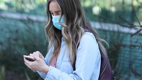Una-Mujer-Con-Una-Máscara-Marca-Su-Teléfono-Durante-La-Epidemia-Pandémica-De-Coronavirus-Covid19