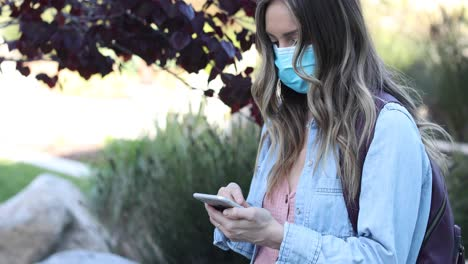 A-woman-in-a-mask-scrolling-her-phone-during-the-Covid19-coronavirus-pandemic-epidemic
