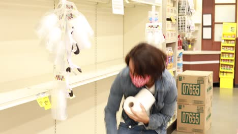 A-man-in-mask-gets-the-last-few-rolls-of-toilet-paper-TP-in-a-supermarket-during-the-Covid19-coronavirus-pandemic-epidemic
