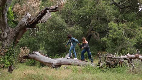 A-Hispanic-couple-walks-on-a-fallen-tree-branch-in-a-park-laughing-and-enjoying-each-others-company