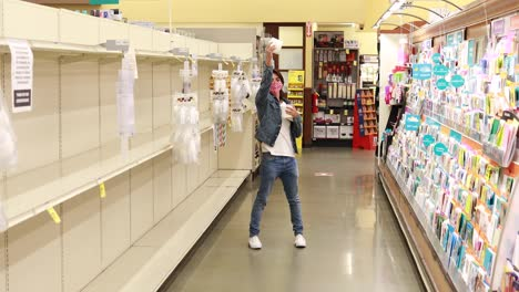 A-man-in-mask-celebrates-finding-the-last-few-rolls-of-toilet-paper-TP-in-a-supermarket-during-coronavirus-pandemic