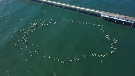 Aerial-over-surfers-in-circle-during-BLM-Black-Lives-Matter-Paddle-For-Freedom-gathering-in-California