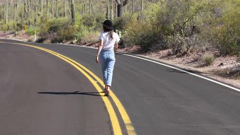 Una-Mujer-Camina-Por-El-Medio-De-Una-Carretera-Del-Desierto-Y-Luego-Se-Vuelve-Para-Mirar-A-La-Cámara