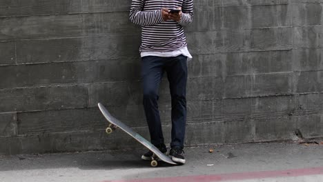 A-man-in-a-Covid-mask-checks-his-phone-on-a-skateboard-during-the-coronavirus-pandemic-outbreak-crisis-2