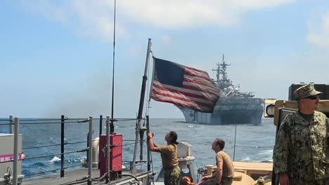 A-Dirty-And-Stained-But-Weathered-American-Flag-Is-Hoisted-From-A-Navy-Ship-At-Sea-In-This-Display-Of-Military-Patriotism