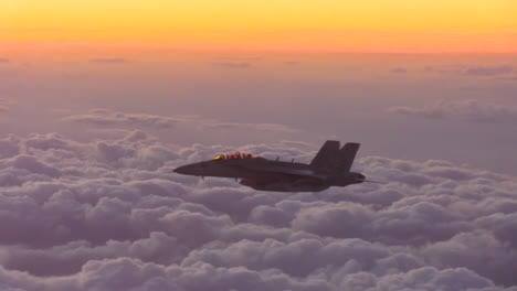 An-American-Fighter-Jet-In-Flight-At-Sunset