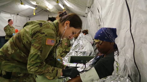 As-Part-Of-A-Us-Armed-Forces-Training-Exercise-A-Soldier-Checks-The-Blood-Pressure-And-Other-Stats-Of-The-Victim-In-A-Simulated-Attack