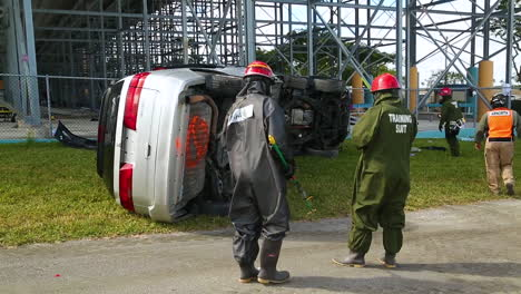 In-A-Joint-Training-Exercise-Firemen-And-Us-Soldiers-Inspect-A-Large-Totaled-Vehicle