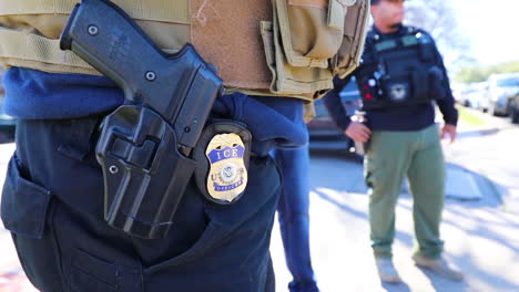 An-Ice-Officers-Badge-And-Gun-Are-Shown-In-Closeup-On-His-Belt
