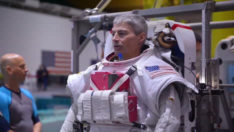 An-Astronaut-Is-Fitted-Into-A-Space-Suit-For-A-Swimming-Pool-Training-Exercise