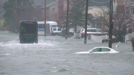 A-Truck-Drives-Members-Of-The-Massachusetts-National-Guard-Through-A-Flooded-Town