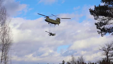 A-Us-Army-Helicopter-Transports-A-Piece-Of-Field-Artillery-As-Part-Of-Exercise-Dynamic-Front-In-Germany
