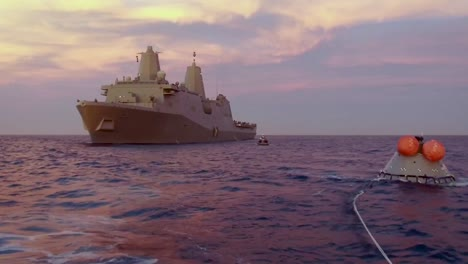 Aerial-Drone-Footage-Captures-the-Recovery-Of-A-Test-Re-Entry-Spacecraft-At-Sea-By-A-Large-Military-Boat-Sunset-2019