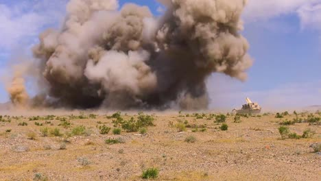 A-Huge-Explosion-Goes-Off-In-Front-Of-A-M1150-Assault-Breacher-Vehicle-thats-Sweeping-A-Battlefield-For-Mines-National-Training-Center-Fort-Irwin-California-2019
