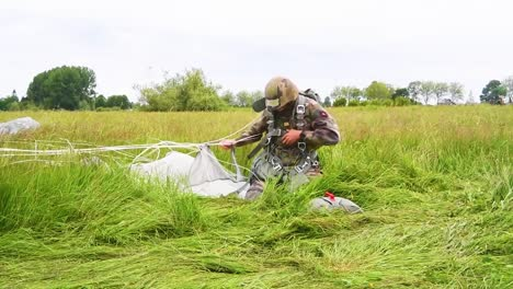 A-Paratrooper-Has-He-Removes-His-Parachute-After-Landing-In-A-Field-Near-Saintemereeglise-France-For-the-75th-Commemoration-Of-Dday-June-9th-2019