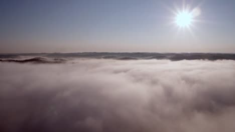 Aerial-Over-Clouds-And-Mountains-With-the-Sun-In-the-Right-Corner
