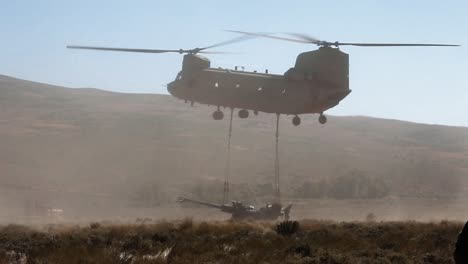 A-Us-Army-Helicopter-Drops-Off-A-Piece-Of-Field-Artillery-Equipment-In-An-Open-Field-And-American-Soldiers-Prepare-It-For-Action