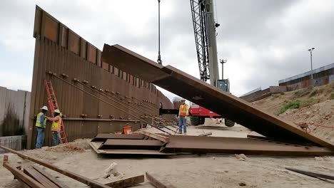 A-Construction-Crane-Is-Used-To-Move-A-Wall-Into-Place-For-A-Building-On-A-Us-Military-Base