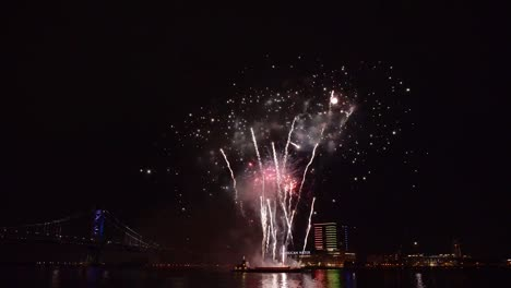 A-Fireworks-Display-Takes-Place-Over-the-Water-By-A-Bridge-In-America
