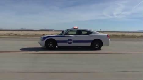 Nasa-Er2-Coming-In-For-A-Landing-And-A-2010-Dodge-Charger-Safety-Chase-Car-Escorting-the-Aircraft-To-A-Safe-Landing-Palmdale-2011