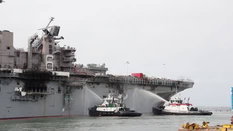 Tugboats-Spray-Water-On-the-Amphibious-Assaul-Ship-Uss-Bonhommer-Richard-To-Cool-the-Skin-And-Prevent-Flash-Fires