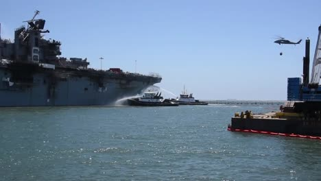 Tugboats-Spray-Water-On-the-Amphibious-Assaul-Ship-Uss-Bonhommer-Richard-To-Cool-the-Skin-And-Prevent-Flash-Fires-1