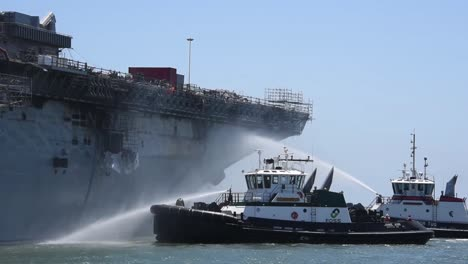 Tugboats-Spray-Water-On-the-Amphibious-Assaul-Ship-Uss-Bonhommer-Richard-To-Cool-the-Skin-And-Prevent-Flash-Fires-2