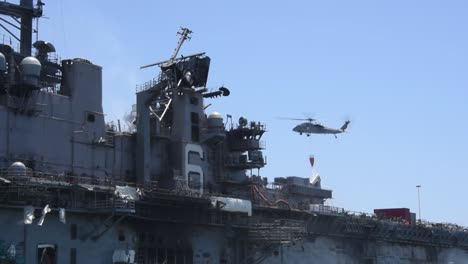 A-Helicopter-Drops-Water-While-Fighting-A-Fire-On-the-Amphibious-Assault-Ship-Uss-Bonhomme-Richard-San-Diego-Ca