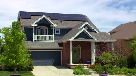 Tilt-Down-To-Solar-Panels-Adorning-The-Tops-Of-A-House-In-A-Residential-Neighborhood