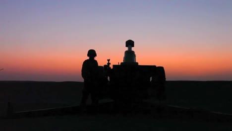 Excelente-Disparo-Al-Anochecer-De-Soldados-Disparando-Cañones-De-Artillería-Contra-El-Enemigo-