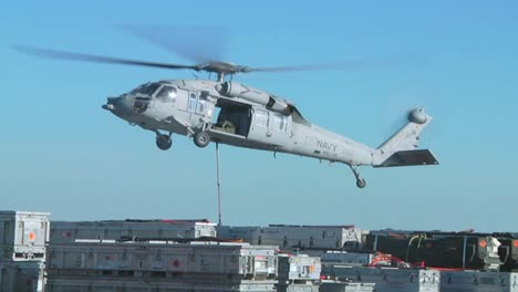 A-Navy-Helicopter-Lifts-Items-Off-The-Deck-Of-An-Aircraft-Carrier-During-A-Operation