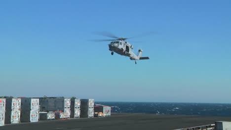 Un-Helicóptero-De-La-Marina-Levanta-Objetos-De-La-Cubierta-De-Un-Portaaviones-Durante-Una-Operación-1