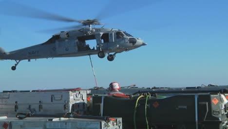 Un-Helicóptero-De-La-Marina-Levanta-Elementos-De-La-Cubierta-De-Un-Portaaviones-Durante-Una-Operación-2