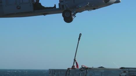 Un-Helicóptero-De-La-Marina-Levanta-Objetos-De-La-Cubierta-De-Un-Portaaviones-Durante-Una-Operación-4