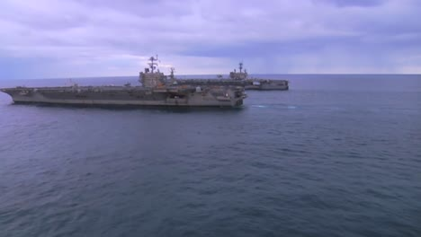 Vista-Aérea-Over-Two-Aircraft-Carriers-On-The-High-Seas-With-Helicopter-Moving-Between-3