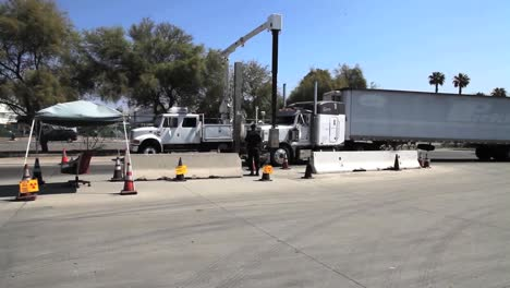 Commercial-Trucks-And-Cars-Passing-Through-The-Us-Mexico-Border-Are-Inspected-By-Border-Patrol-Agents-Using-Radiological-Devices