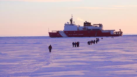People-Walk-Across-Ice-Floes-To-Get-To-A-Us-Coast-Guard-Breaker-Ship